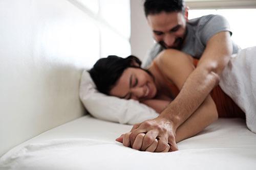 ベットで手を繋ぐ男女